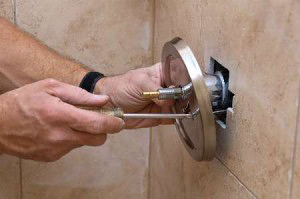 Plano TX plumbing contractor repairs a shower knob with a phillips head
